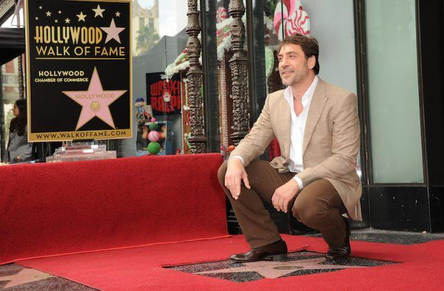 Javier Bardem kneels close to his star.
