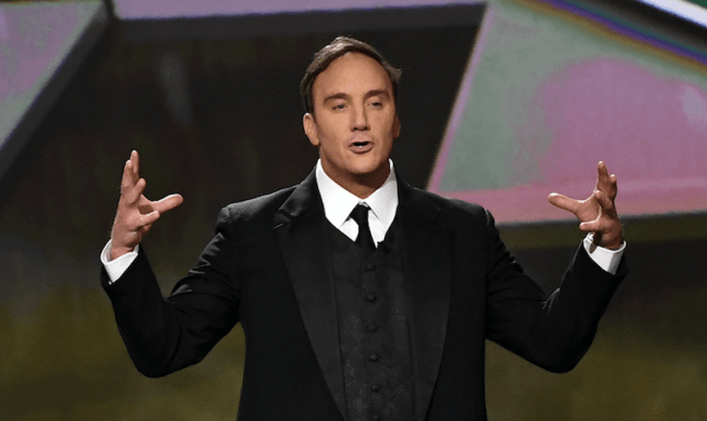 Jay Mohr stands in a tux with his hands up