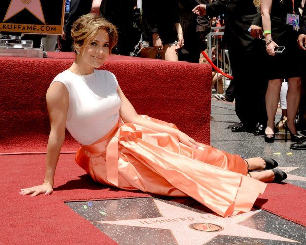 Jennifer Lopez sits in front of her star.