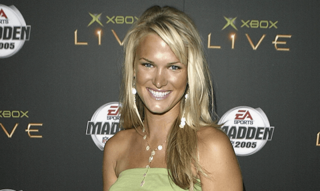 Jessica Bowlin smiling brightly as she stands in a green top at a video game event.