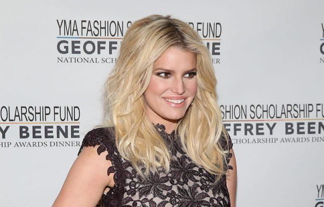 Jessica Simpson smiling while standing at a red carpet event.