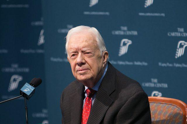 Jimmy Carter in front of a microphone.