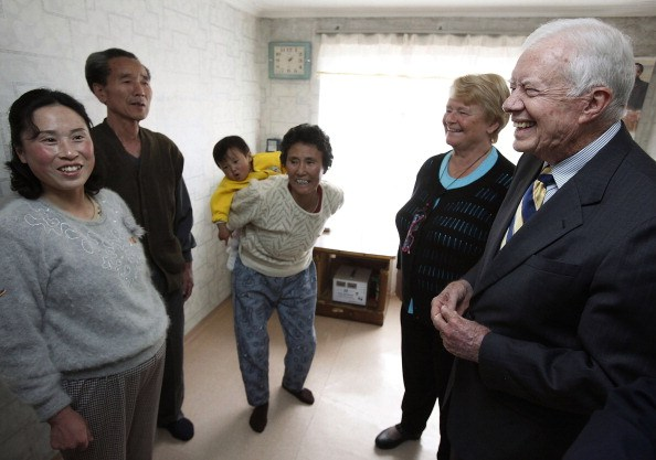 Jimmy Carter (R) and former Prime Minister of Norway Gro Brundtland (2nd R) chat with a family during a house visit on April 27, 2011, in Pyongsong, North Korea