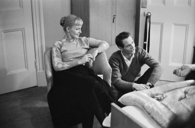 Joanne Woodward and Paul Newman sitting together in an apartment.
