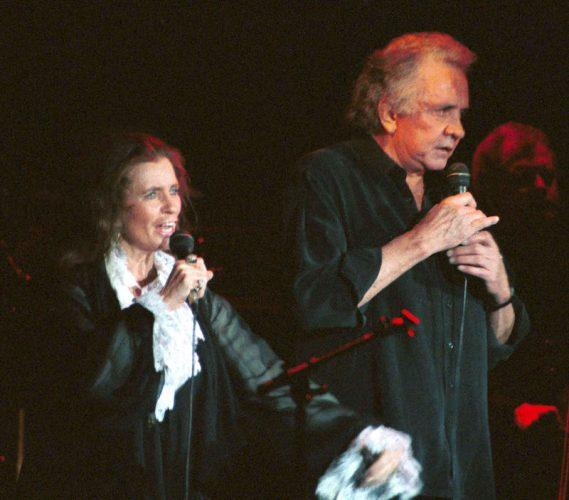 June Carter and Johnny Cash performing on stage.