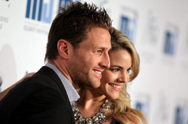 Juan Pablo Galavis and Nikki Ferrell stand close to each other as they smile at photographers.