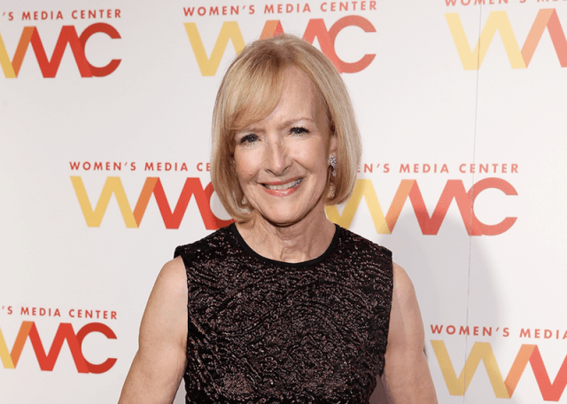 Judy Woodruff smiles and stands in a sequined gown at an event.