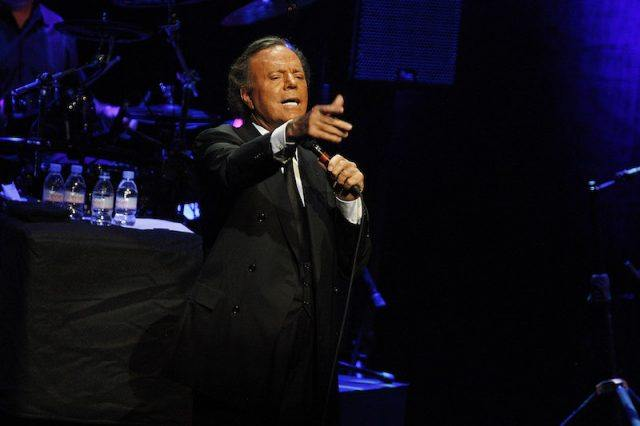 Julio Iglesias performing on stage while holding a microphone.
