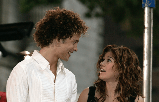 Justin Guarini and Kelly Clarkson smile at each other while performing on stage.