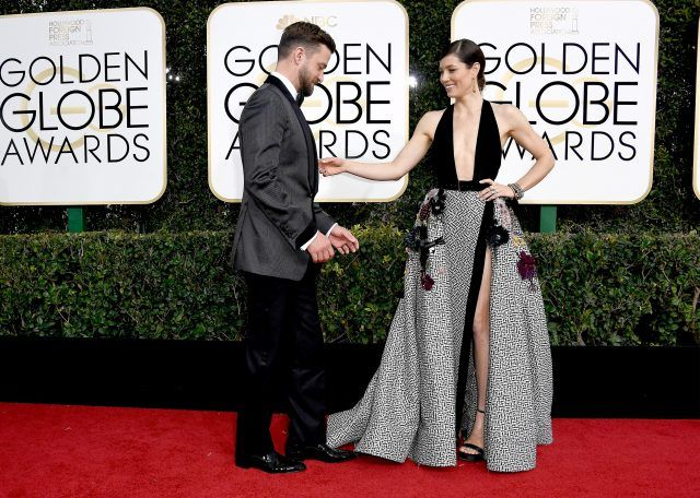 Justin Timberlake and Jessica Biel playfully posing on a red carpet.