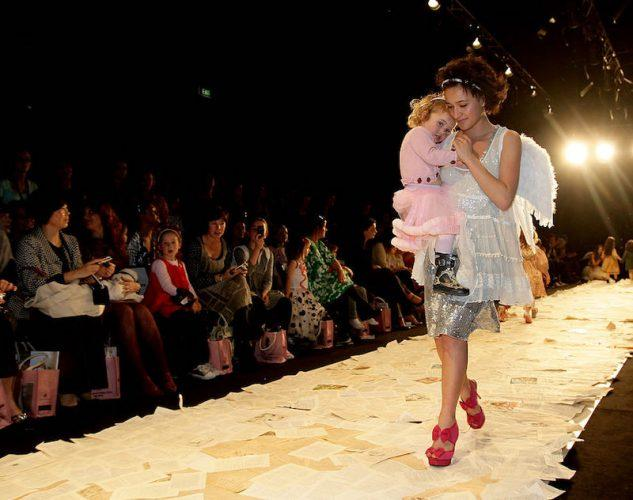 Keisha Castle-Hughes walking down a fashion catwalk with her baby in 2009.