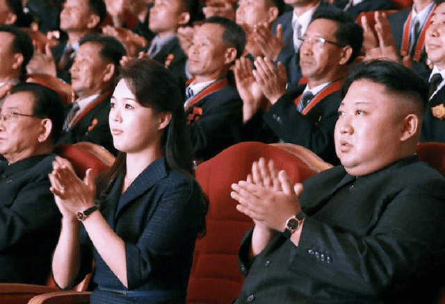 Ri Sol Ju applauding and sitting next to her husband in an auditorium.
