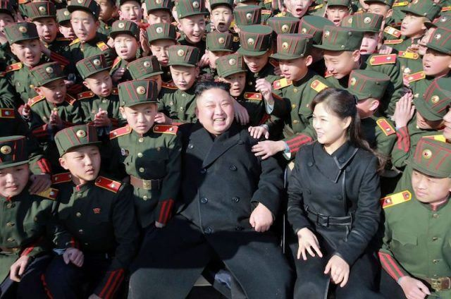 Kim Jong Un sitting with his wife and young military students.