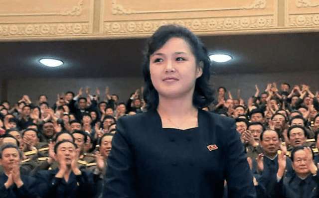 Ri Sol Ju stands in a courtroom full of military officials.