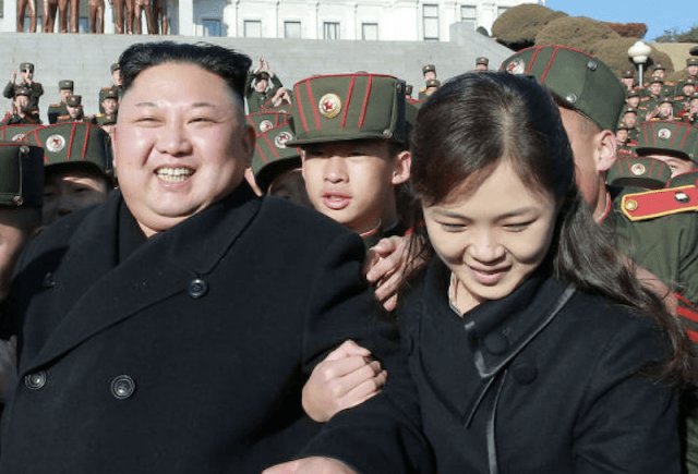 Ri Sol Ju grabbing Kim Jong Un's arm and leading him through a crowd of military students.