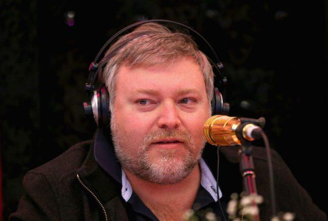 Kyle Sandilands sitting in front of a microphone while wearing headphones.