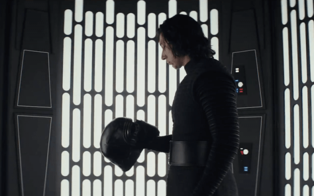 Kylo Ren holding his black helmet in his right hand as he looks downward at it.