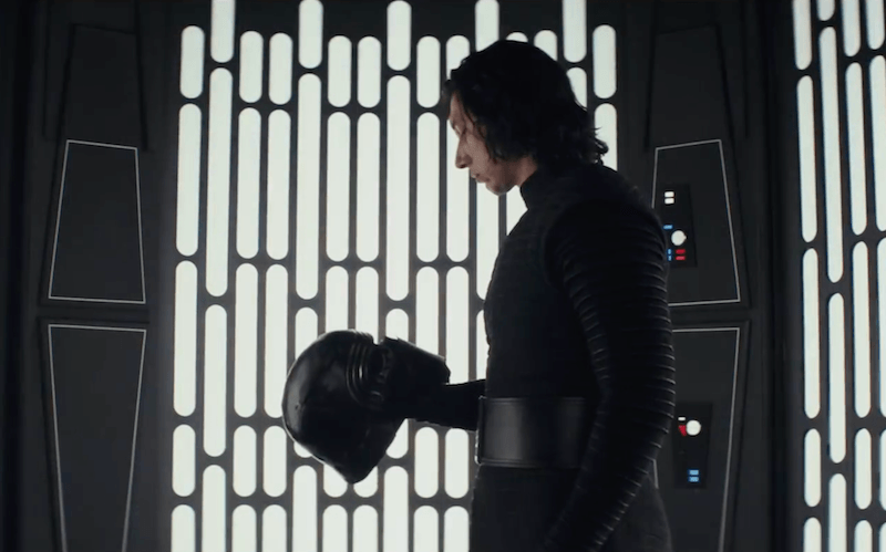 Kylo Ren in Star Wars: The Last Jedi staring at his helmet.