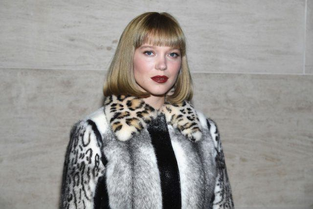 Léa Seydoux in a fur jacket in front of a wooden table.