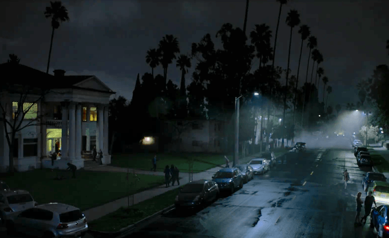 An LA street with parked cars and palm trees