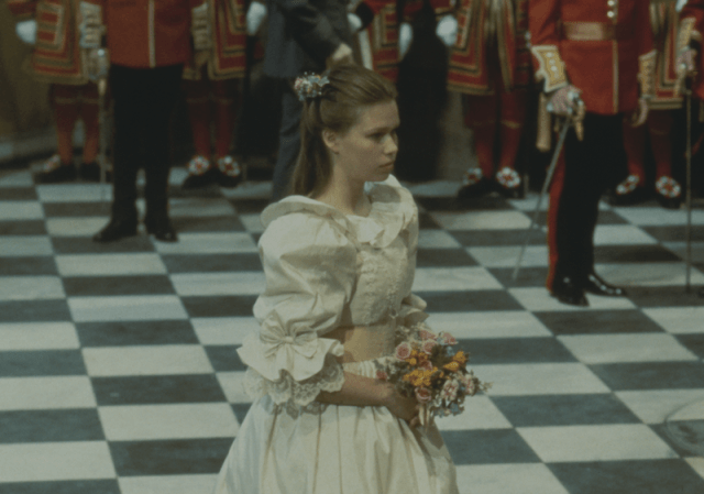 Lady Sarah Spencer walking down the aisle holding flowers.