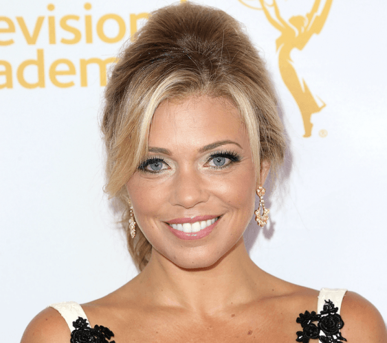 Lauren Sivan smiling while wearing a black and white dress and gold earrings.