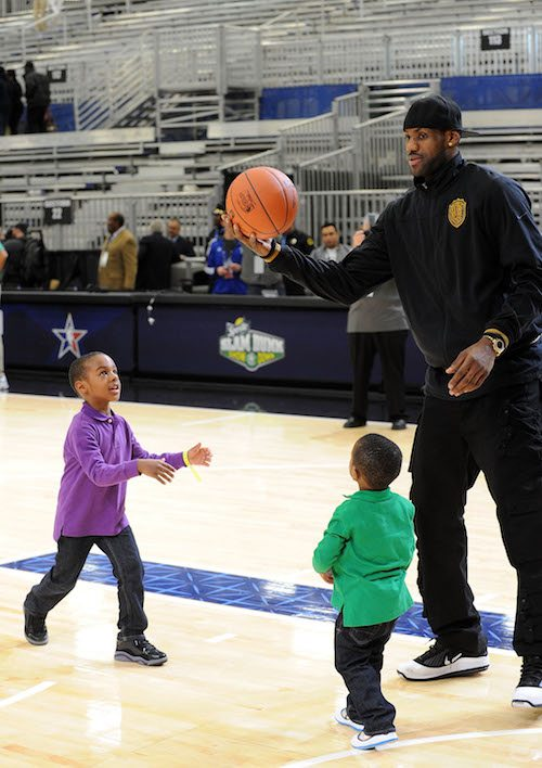 LeBron James playing basketball with two of his sons.