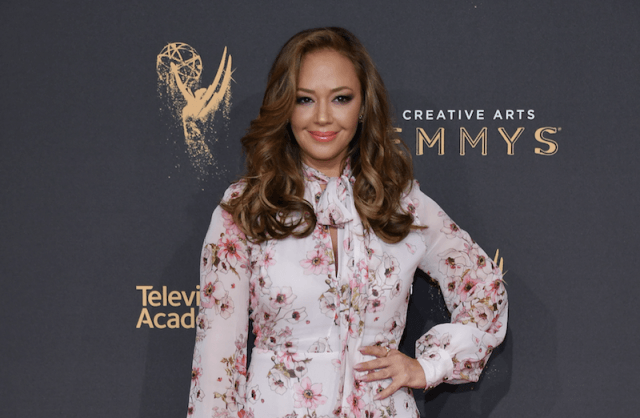 Leah Remini standing with one hand on her hip while posing for photos on a red carpet.