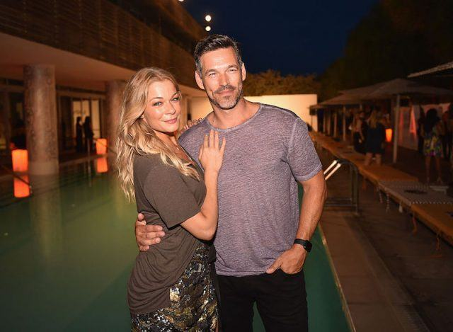 Eddie Cibrian and LeAnn Rimes standing in front of a pool.