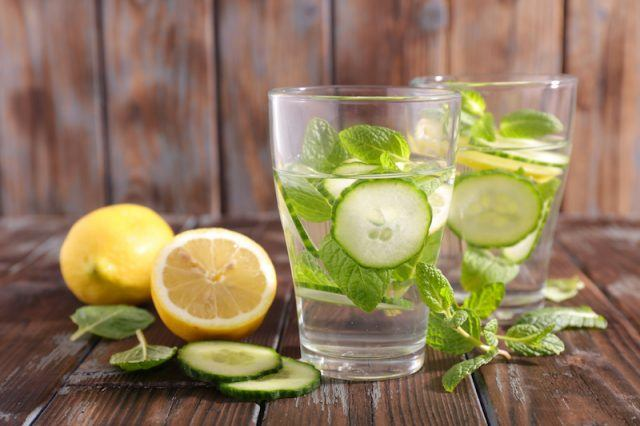 Glasses of water with lemon, mint and cucumber slices.