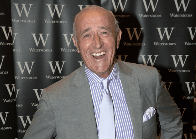 Len Goodman standing in a gray suit and silver tie as he laughs.