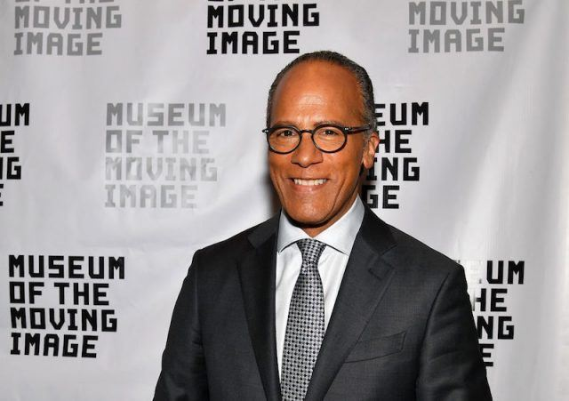 Lester Holt stands in a suit and glasses while smiling at a museum event.