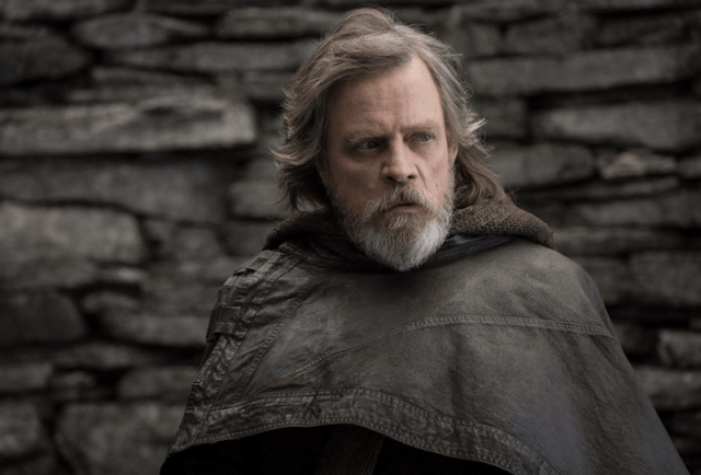 Luke Skywalker stands in a brown cloth in front of a brick wall as he looks towards the side.