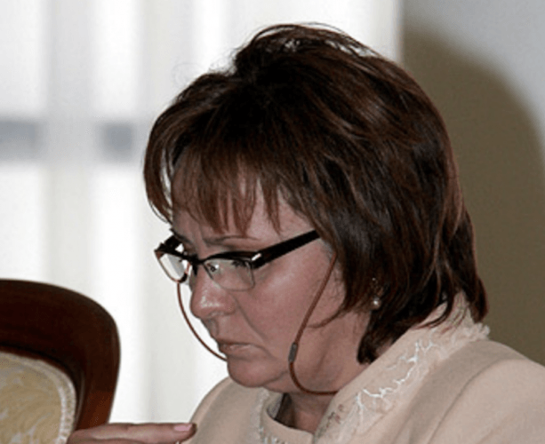 Lyudmila Ocheretnaya wearing dark glasses and reading something on her desk.