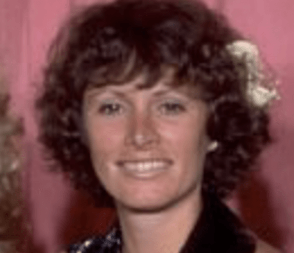 Marcia Lucas smiling brightly while standing in front of a pink curtain.