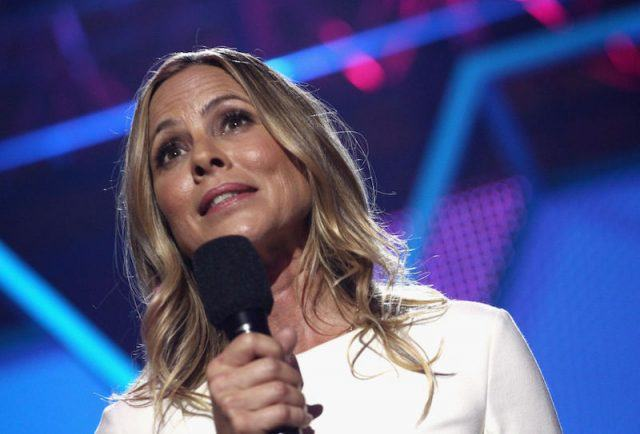 Maria Bello holding a microphone while standing on stage.