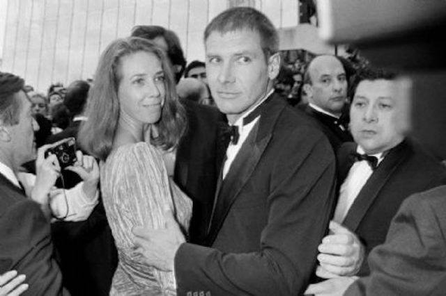 Mary Marquardt and Harrison Ford standing among a group of party guests and photographers.