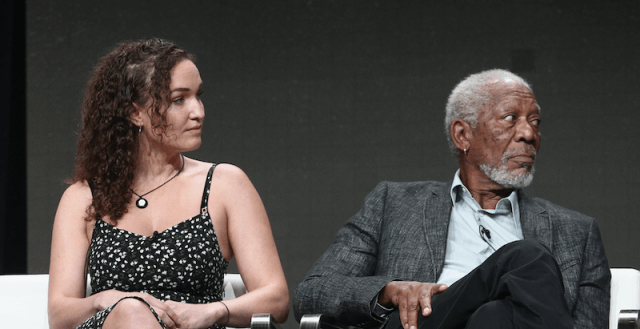 Megan Phelps-Roper sits with Morgan Freeman as they both turn their head to the side during a panel.