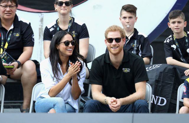 Harry and Meghan smile and clap while sitting on the stands at Invictus Games.