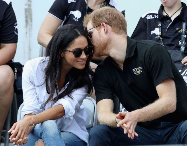 Harry whispers something into Meghan's ear during the games.