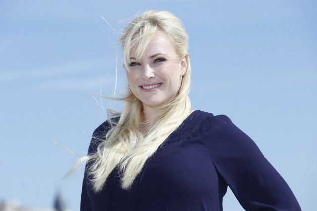 Meghan McCain poses in front of a blue sky.