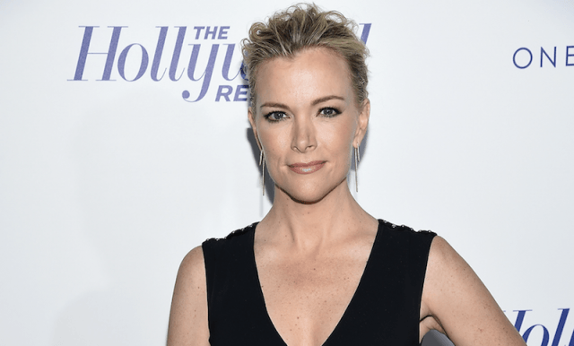 Megyn Kelly standing in a black sleeveless gown as she smiles slightly towards the camera.