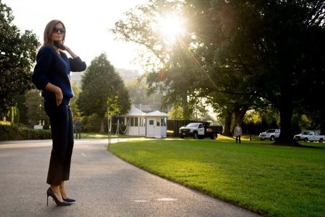 Melania Trump standing on a road with heels, sunglasses and a blue sweater.