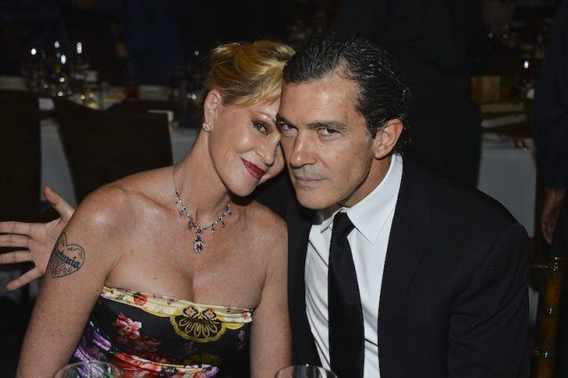 Melanie Griffith and Antonio Banderes sitting closely together during a dinner.