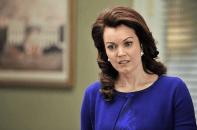 Mellie Grant stands and looks downward while wearing a blue dress in her office.