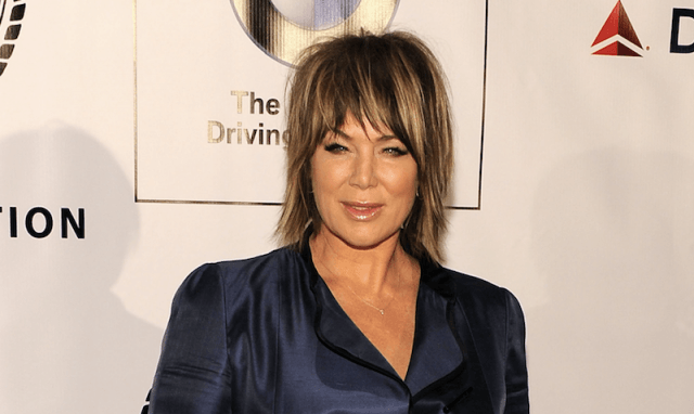 Mia Michaels in a blue blazer standing on the red carpet of an event.