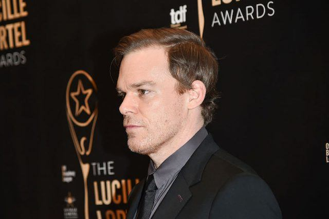 Michael C. Hall poses for photos in a black suit on a red carpet.