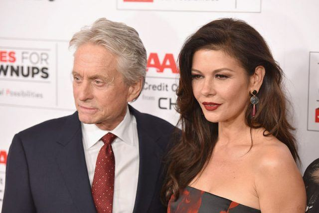 Michael Douglas and Catherine Zeta-Jones stand together as they pose for photos at a red carpet.