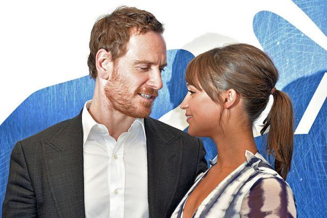 Alicia Vikander and Michael Fassbender looking at each other while posing for photographers.