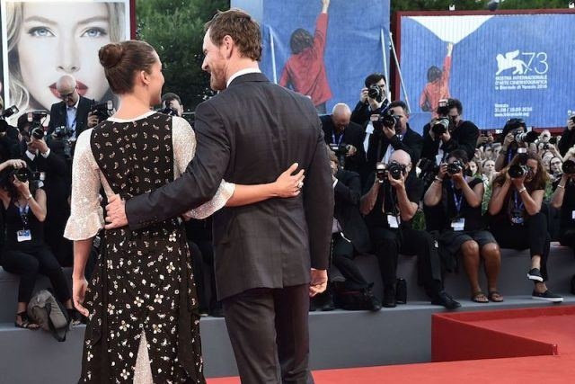 Michael Fassbender and Alicia Vikander hold each other while posing for photographers at a red carpet.